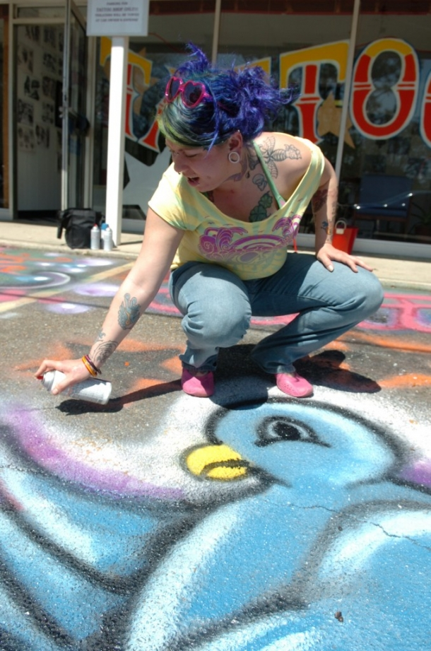 Skipper, a tattoo artist from Colorado Springs, spray paints a bird on the pavement in front of Wicked Addiction Ink on Tuesday afternoon. Skipper, who is friends with owner Blaine McCullough, said she wanted to bring some attention to the shop with her colorful art. (Erin Parker / The Hattiesburg American)