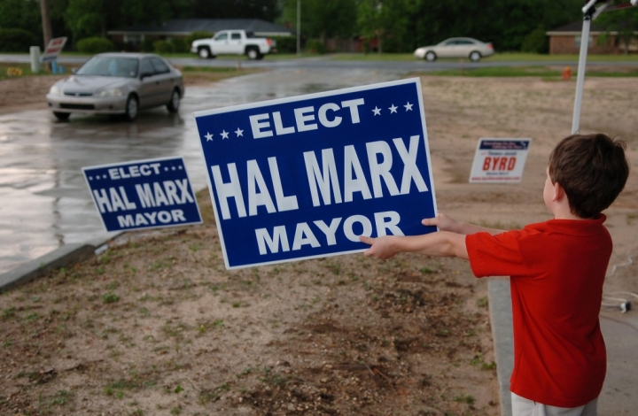Nathan Marx, 7, holds up a sign for his father Tuesday night at Calvary Baptist Church in Petal. Precinct workers at the church said more than 600 people cast their ballots during the day. (Photo by Erin Parker / The Hattiesburg American)