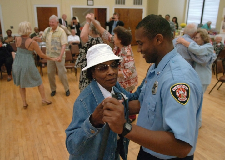 Hattiesburg firefighter Elliott Edwards dances with Janice Sanders during the City of Hattiesburg