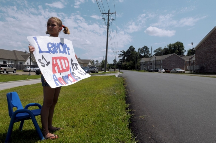 Hannah Harvison, 8, holds a sign advertising the lemonade stand Friday afternoon at the Crayon College. Children and teachers from the Crayon College used the stand as a fundraiser for the Lumberton Animal Sanctuary. (Photo by Erin Parker / The Hattiesburg American)