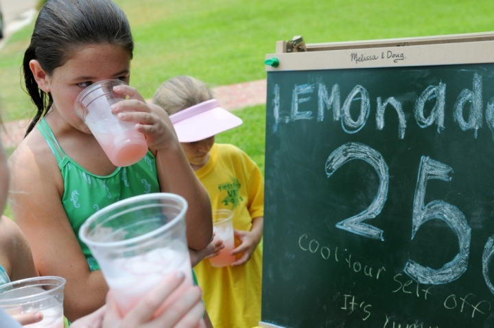 Ainsley Richardson, 10, sips lemonade out of a cup Monday afternoon at the lemonade stand on the corner of Heatherwood and Colony Lane. Jackson and Olivia Chandler, from McKinney, Tex., set up shop in their grandmother