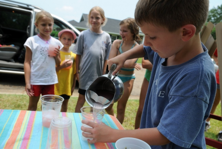Jackson Chandler, 8, pours lemonade into a cup as his customers watch Monday afternoon at her grandmother