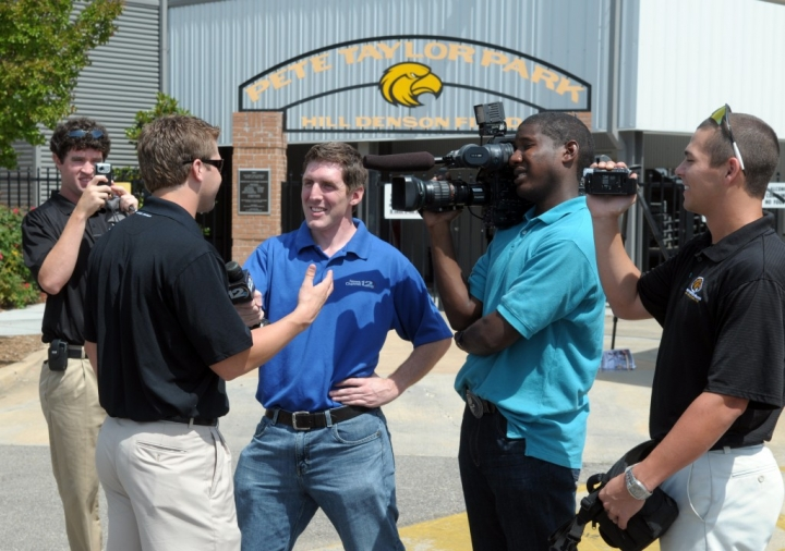 Southern Miss players Jonathan Johnston, left, and Corey Stevens, right, film Chris Williams, middle right, and Jason Hurst interviewing Brian Dozier before the Golden Eagles departed from Pete Taylor Park for the Pine Belt Regional Airport Thursday morning. The Golden Eagles will face the Texas Longhorns Sunday during their first game of the College World Series. (Photo by Erin Parker / The Hattiesburg American)