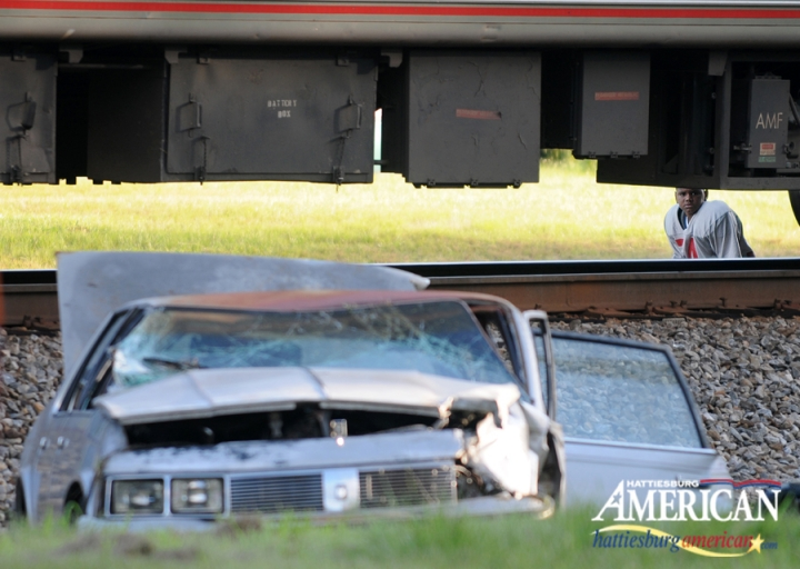 A boy peers beneath the train to look at a wrecked vehicle after it was struck by a westbound Amtrak train around 5 p.m. Friday afternoon near the intersection of 6th Avenue and Railroad Street. (Photo by Erin Parker / The Hattiesburg American)