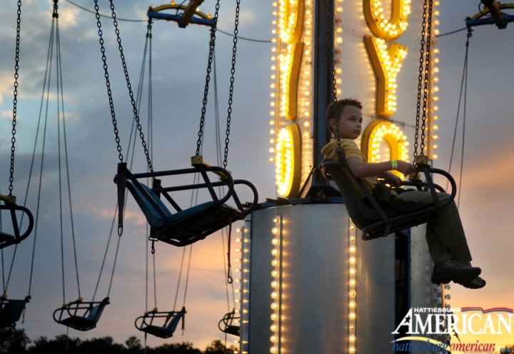 Rice Patrick, 8, and his friends are lowered after riding the swings Wednesday night at the Fair of Forrest County. (Photo by Erin Parker / The Hattiesburg American)