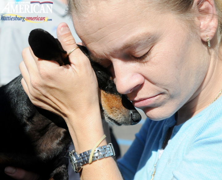 Staci Williams closes her eyes and holds family dog Daisy close Tuesday morning at Oak Grove