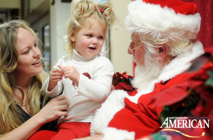 Mailee, 3, of Oak Grove, tells Santa what she wants for Christmas as she is held by her mother, Mandy,Thursday afternoon at the Oak Grove Public Library. Children and their parents came to the library to take pictures with Santa. (Photo by Erin Parker / The Hattiesburg American)
